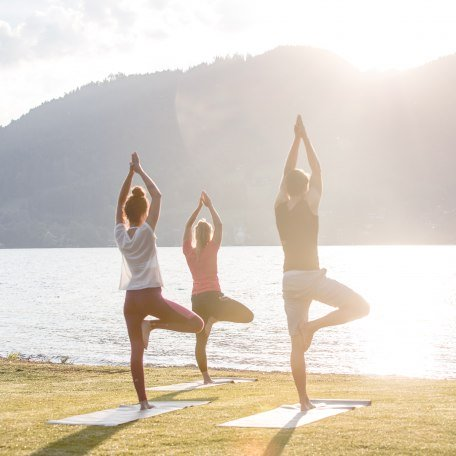 Mit viele Geschick balanciert die Yogaklasse bei dieser Übung in der Sonne am Ufer des Tegernsees, © Hansi Heckmair