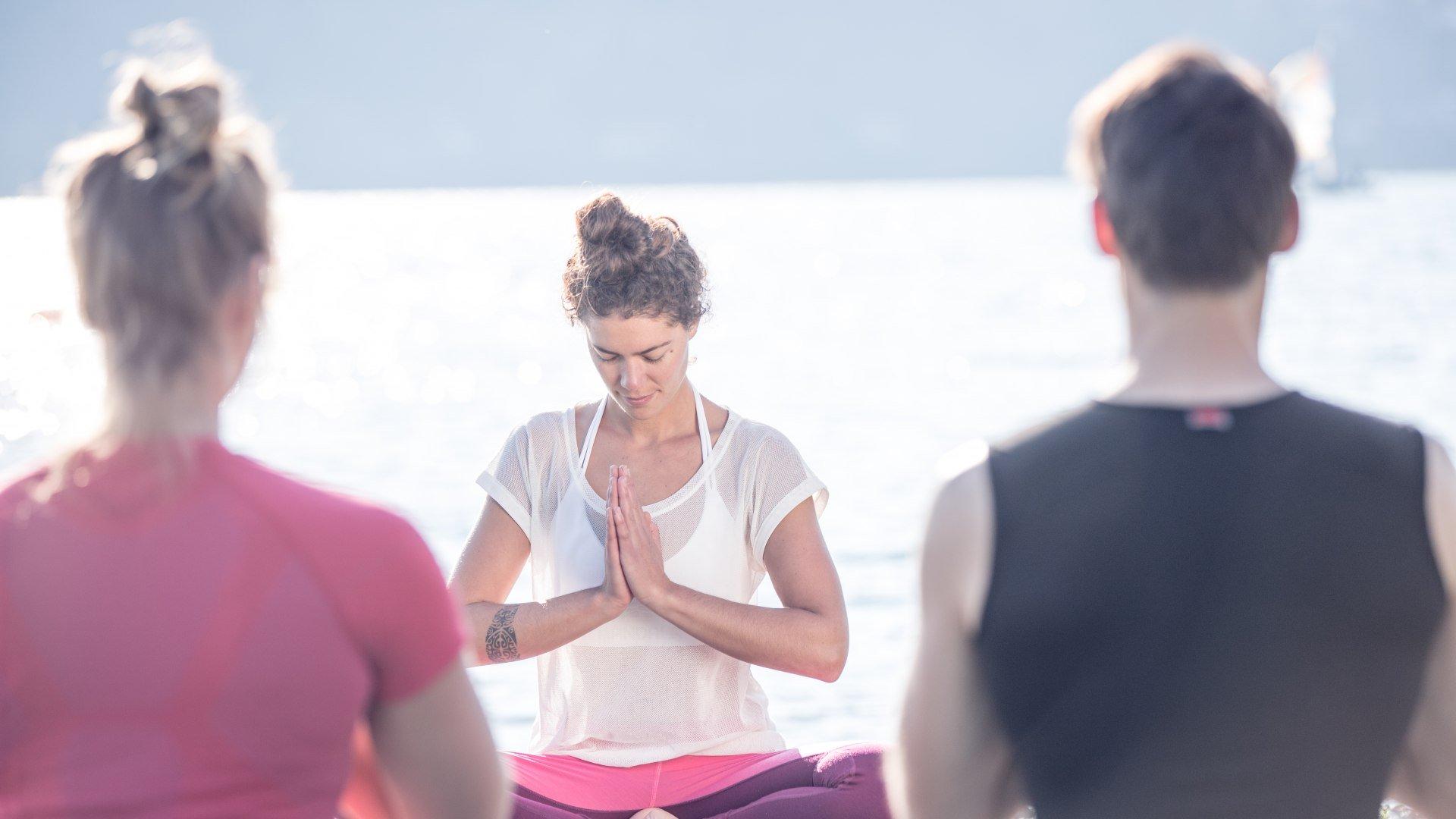 Mit dem Abschiedsgruß Namaste beendet die Yogalehrerin ihre Yogastunde unter dem blauen Himmel am Ufer des Tegernsees in Bad Wiessee., © Hansi Heckmair