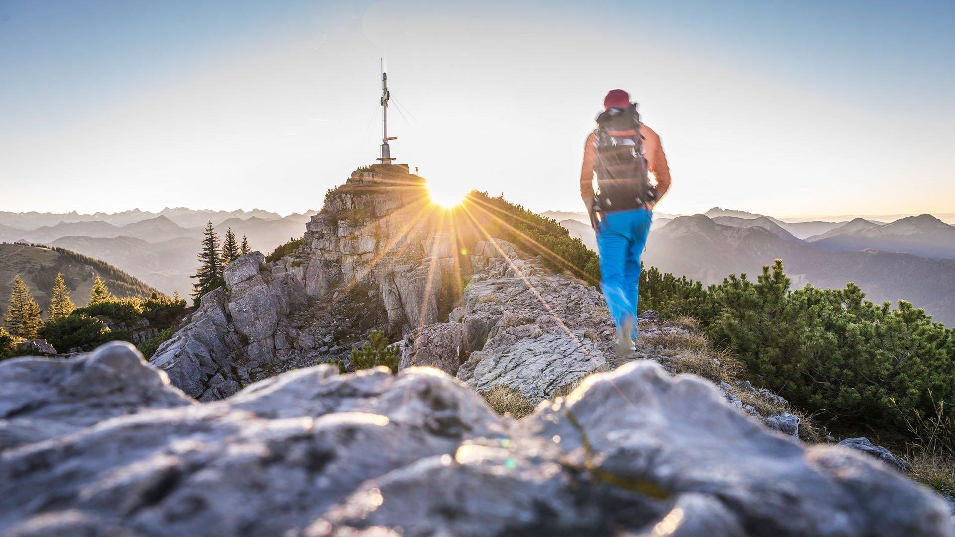 Wanderer bei Sonnenaufgang kurz vor dem Gipfelkreuz Wallberg, © Dietmar Denger