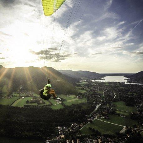 Paraglider fliegt dem Tegernsee und der Sonne entgegen, © Dietmar Denger