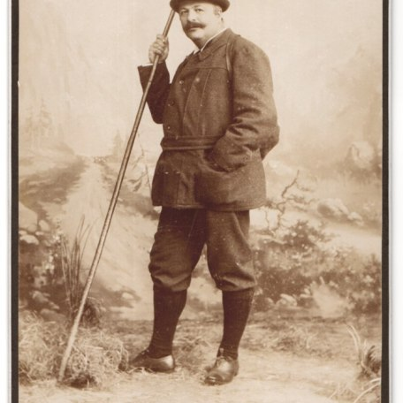 Fotografie-E-Ganghofer-Egern-am-Tegernsee-Portrait-Mann-in-Wanderkleidung-mit-Wanderstock-im-Atelier, © Dr. Peter Czoik