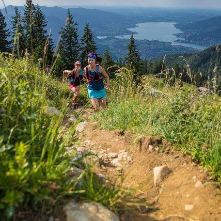 Ein schmaler Trail führt den Berg hinauf im Hintergrund sieht man zwei Läuferinnen und den Tegernsee., © Hansi Heckmair