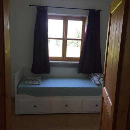 1. kleines Schlafzimmer Bett ist ausziehbar, kleiner Tisch mit zwei Stühlen und kleinem Schrank., © im-web.de/ Alpenregion Tegernsee Schliersee Kommunalunternehmen