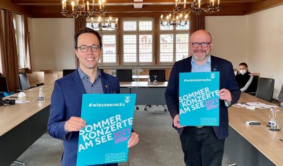 Der Wiesseer Bürgermeister Robert Kühn (l.) präsentiert mit TTT-Geschäftsführer Christian Kausch das neue Plakat #wiesseerocks .  , © Der Tegernsee