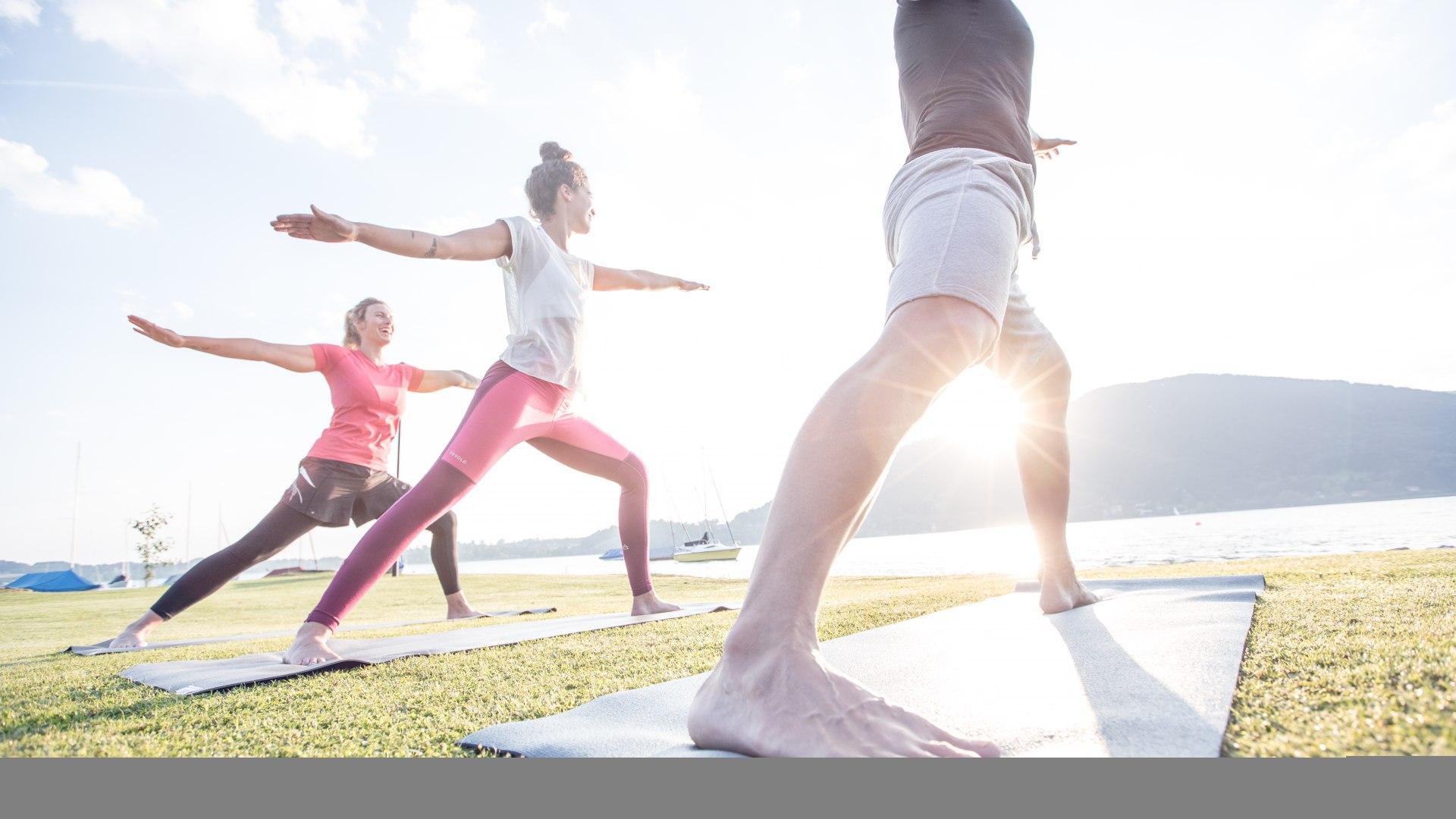 Yogaklasse hat Spaß bei morgendlichen Übungen im Sonnenschein am Ufer des Tegernsees in Bad Wiessee, © Hansi Heckmair
