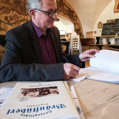 Während eines Interviews im Bräustüberl im Tegernsee werden Notizen gesichtet., © Stefanie Pfeiler