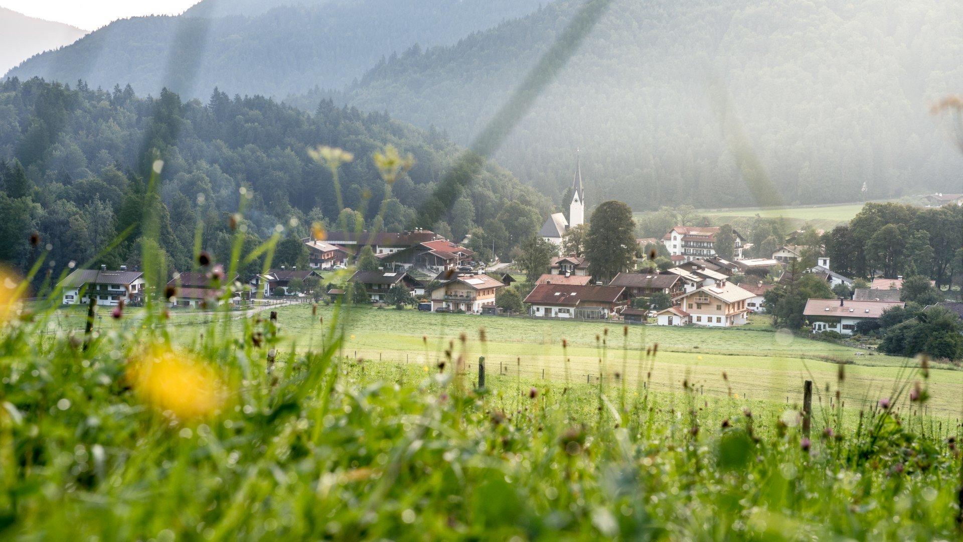 Der Blick über eine saftige Wiese auf den Ort Kreuth, © Julian Rohn