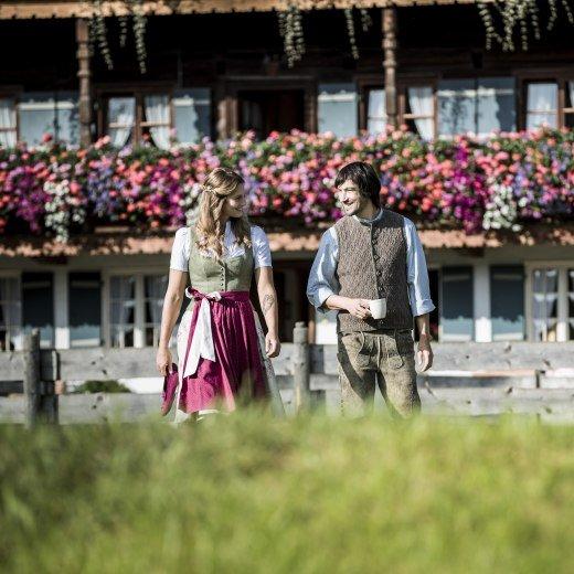 Pärchen in Tracht, schlendert über Blumenwiese vor altem mit Geranien geschmücktem Bauernhaus., © Hansi Heckmair