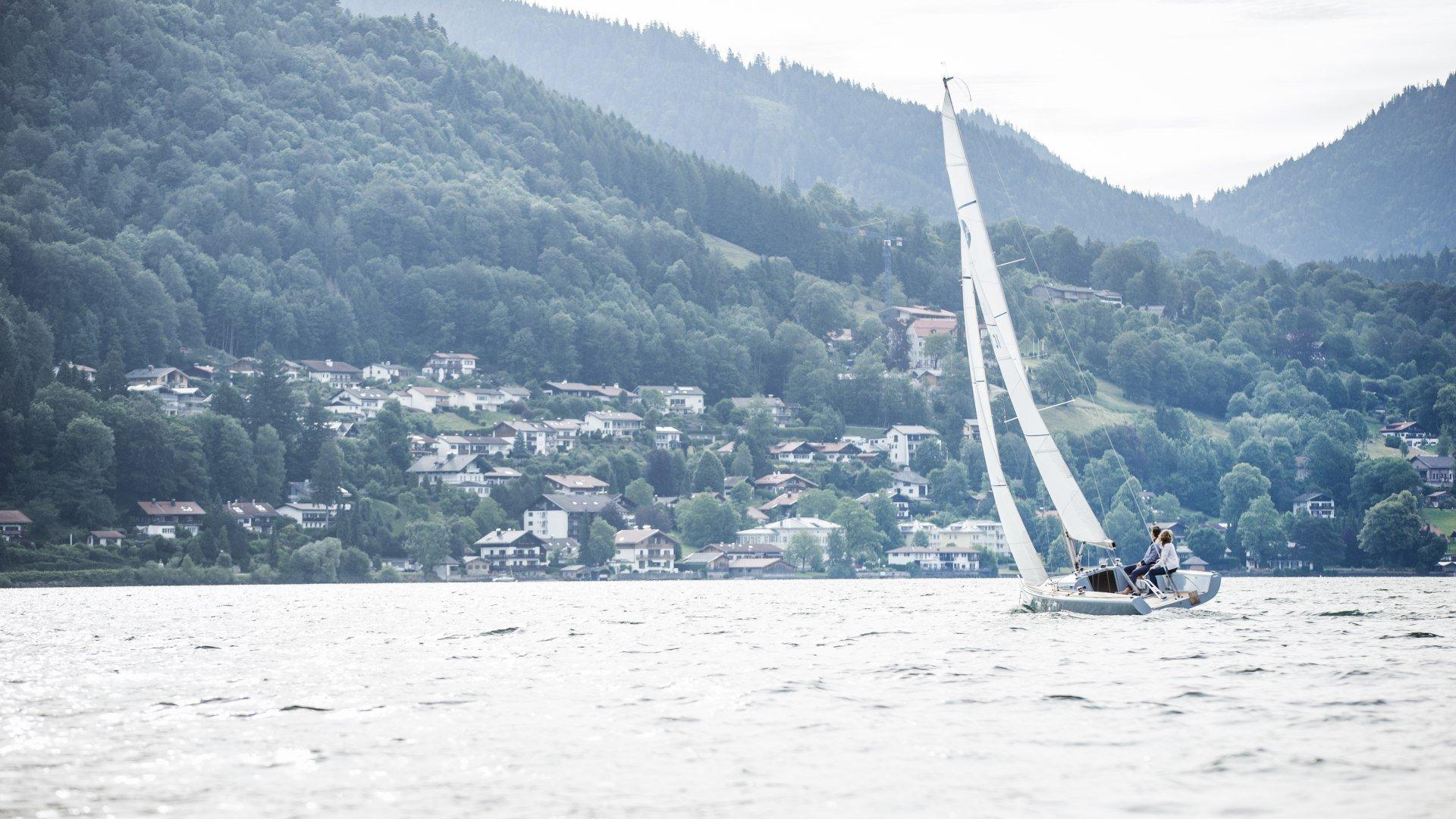 Ein Segelboot segelt auf dem Tegernsee mit Blick auf Stadt Tegernsee., © Hansi Heckmair