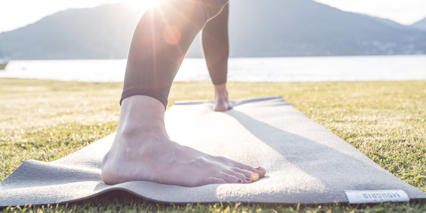 Die Sonne spitzt über die Berge und die Füße stehen fest auf der Matte bei der Yogaübung am Ufer des Tegernsees, © Hansi Heckmair